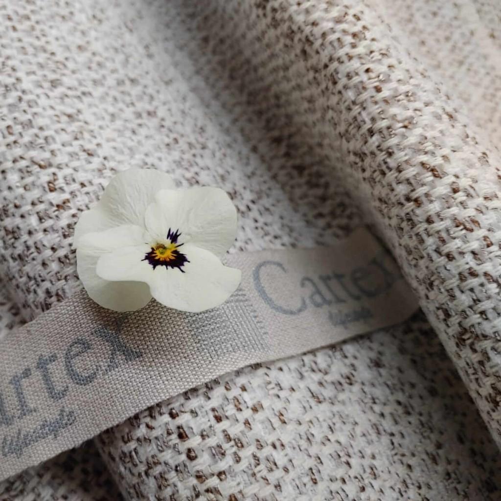 Tessuti con colori neutri e fiore bianco