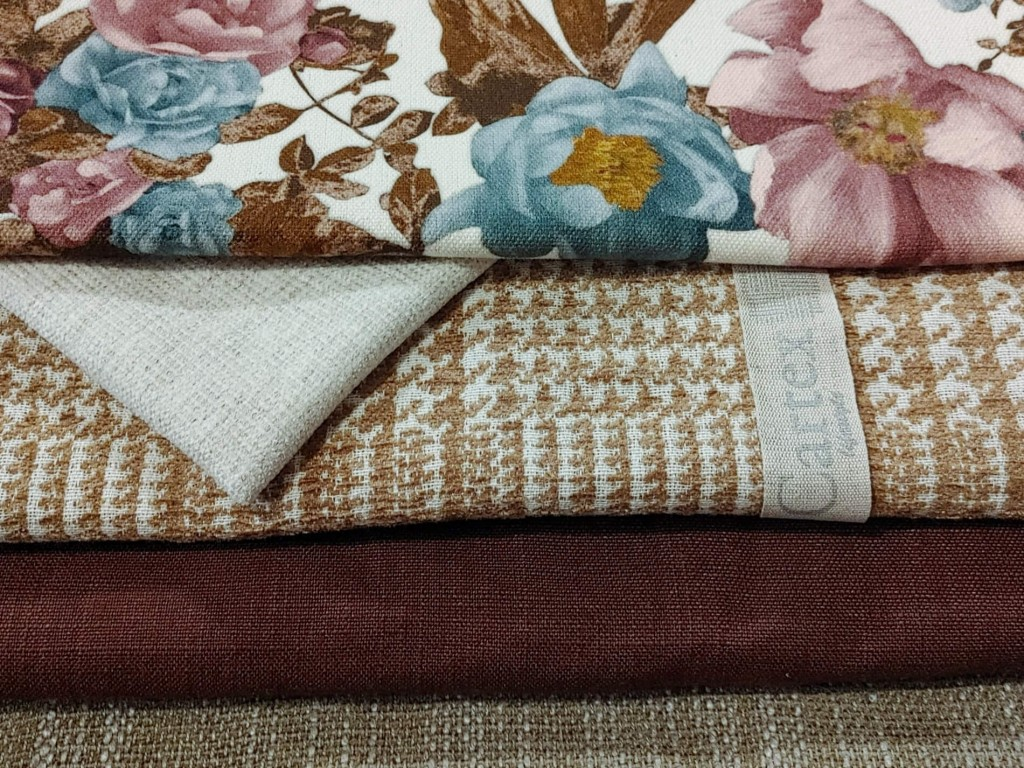 Various floral and unfolded fabrics arranged on top of each other