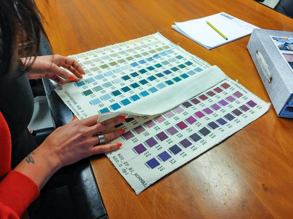 Hands with red nail polish on their fingers flicking through the colour chart of a fabric printer