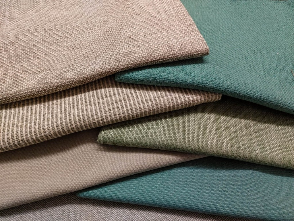 composition of six sofa fabrics in soft colours folded and overlapped