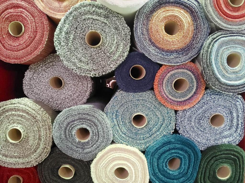 Rotoli di tessuto colorato ammucchiati su uno scaffale