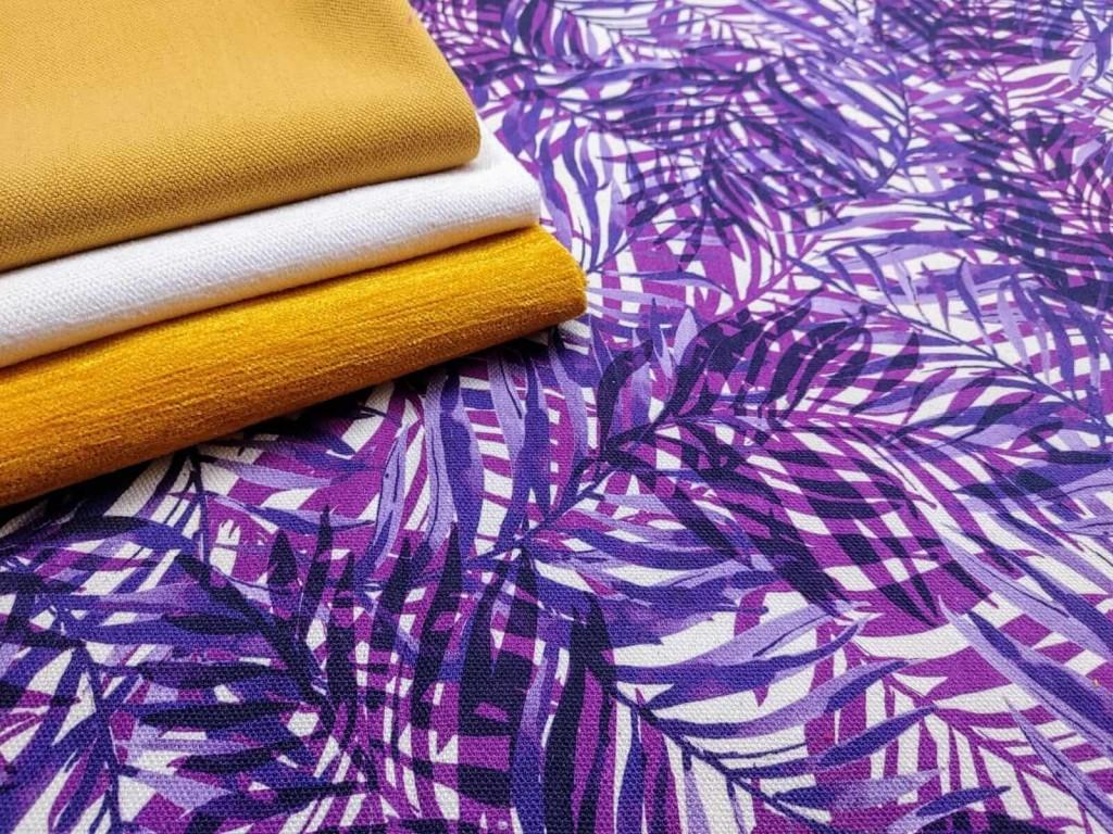 Composizione di tessuti colorati stampati a foglie viola e tinta unita giallo e bianco